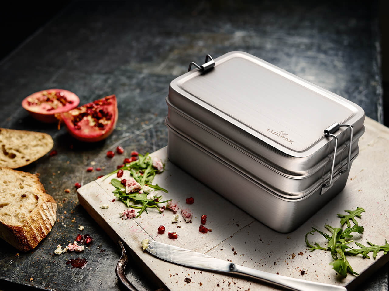 A computer generated image of a stainless steel container on a bread board with remainders of food from a finished lunch