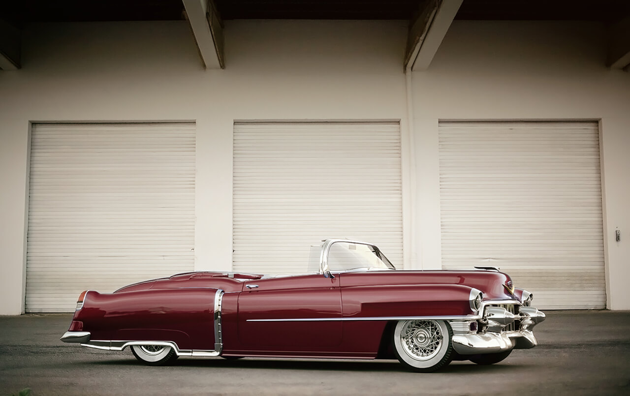 Image of a classic dark red Cadillac in front of Commercial garage doors