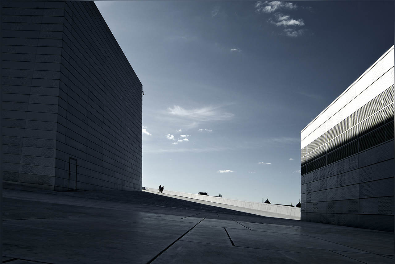 An Image of two distant people walking across the top of a modern roof with buildings
