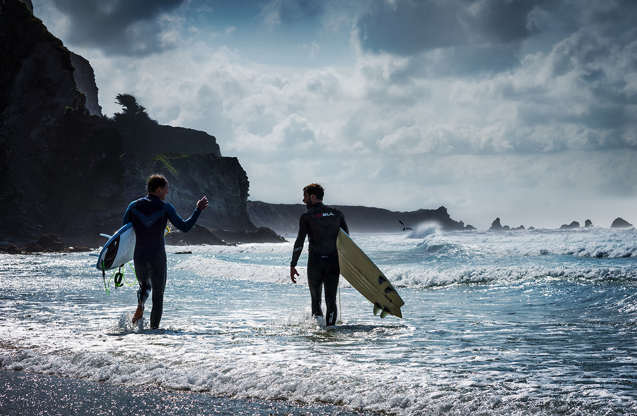 Image of two surfers entering a breezy coastal sea