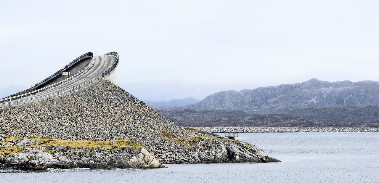 Image of a steep curving road on a steep coastal ridge surrounded by sea and mountains