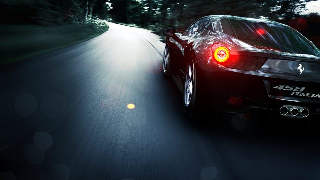 Computer generated image of a black sports car speeding along a road