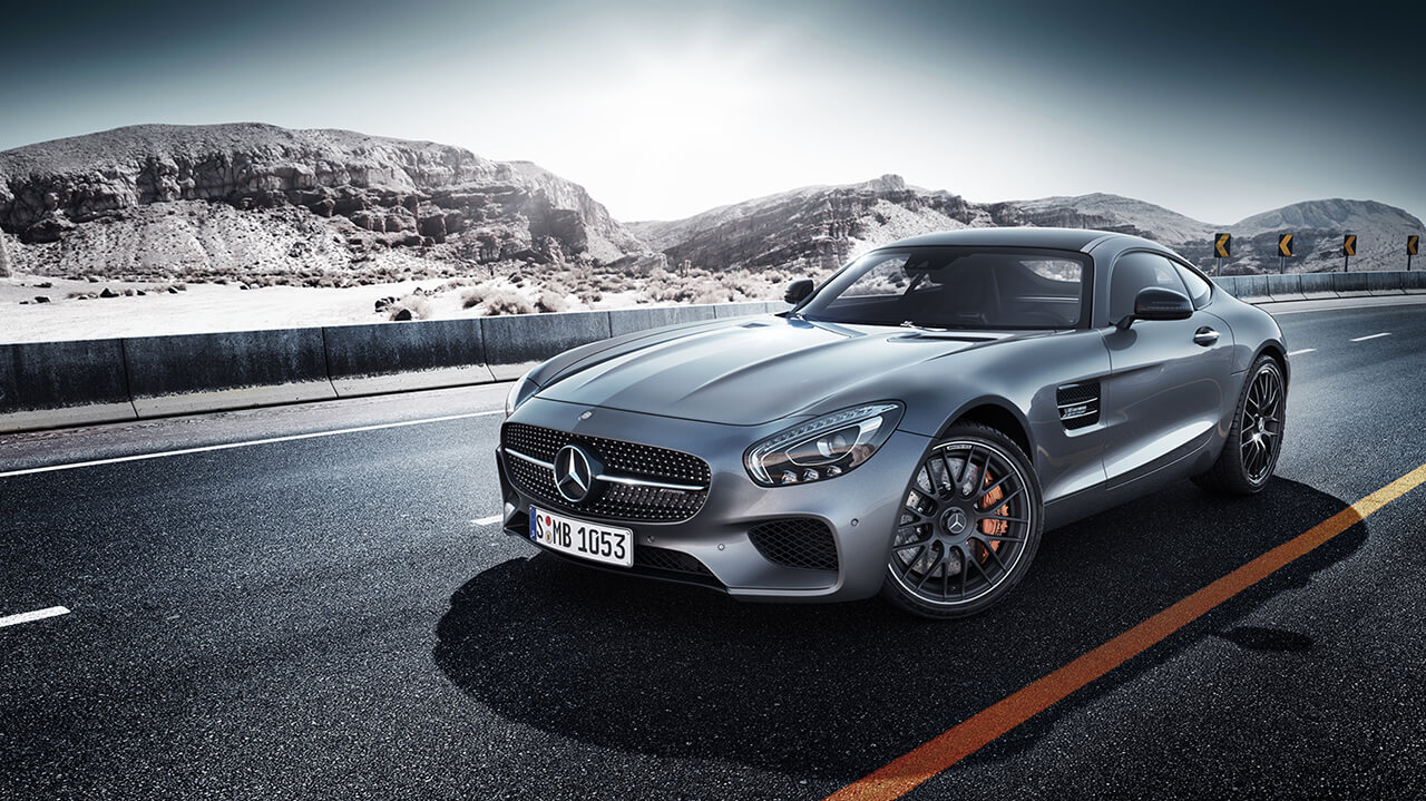 Image of Grey sports car on road with icy mountains in background