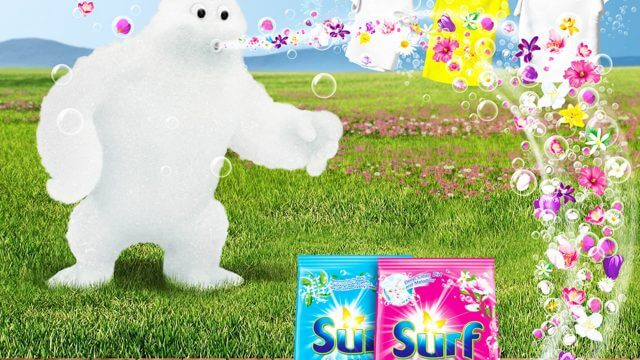Computer Generated Image of a friendly monster made from foam blowing bubbles made of flowers into a pack of washing powder on a decked patio in a garden with washing hanging out to dry