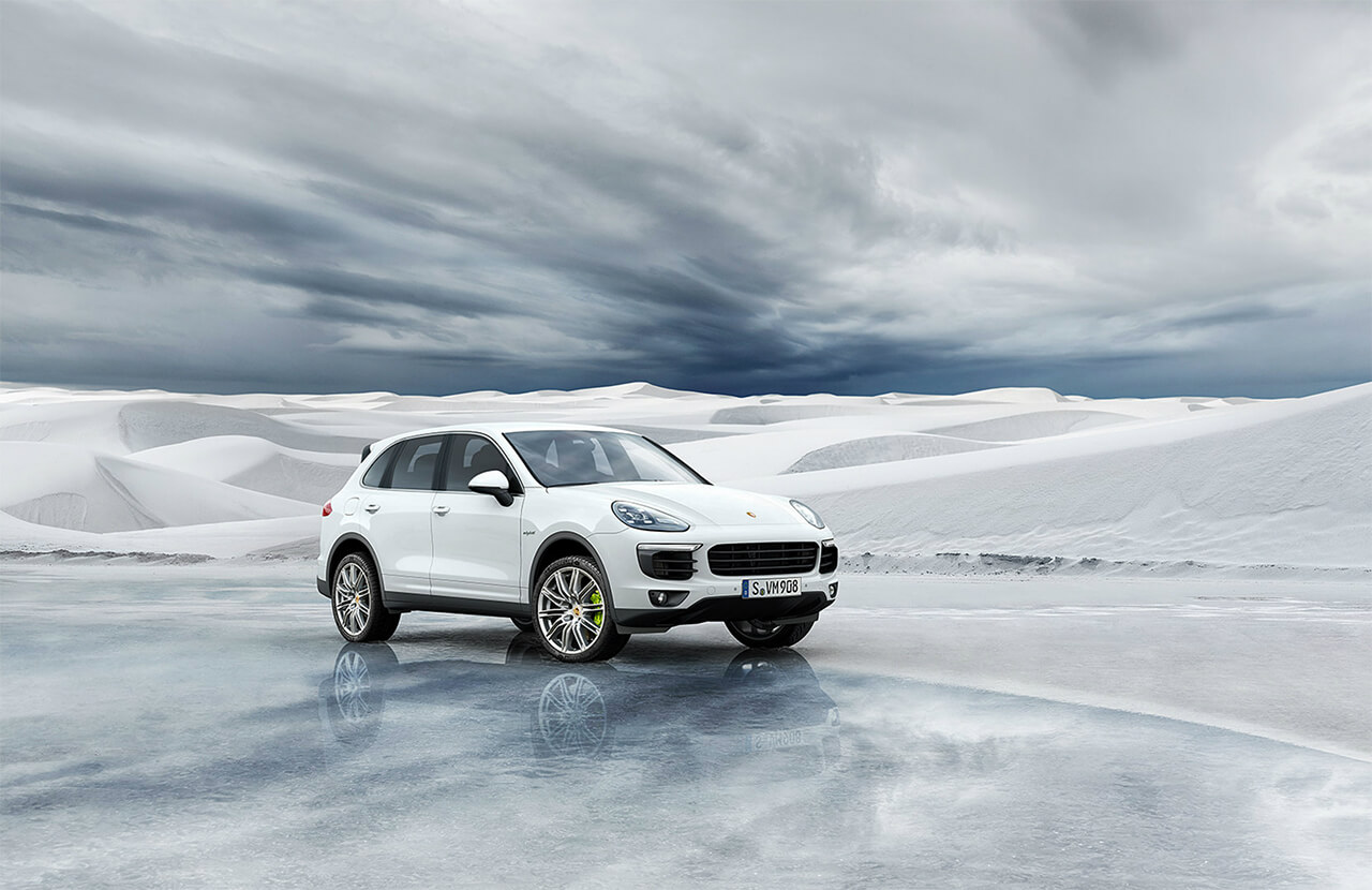 An Image of a Porsche Cayenne Car on and icy road with snowy mounains