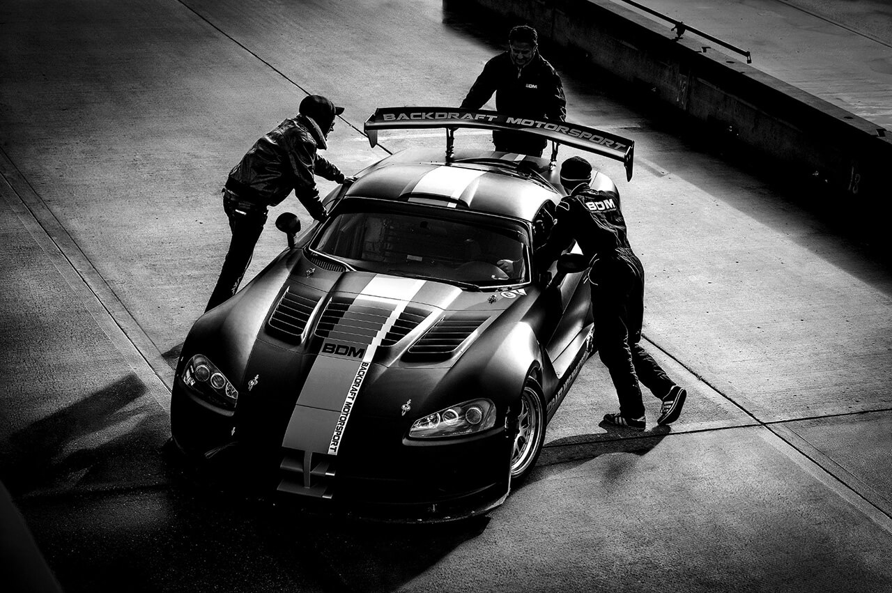 Black and White Image of racing car with crew in pit lane