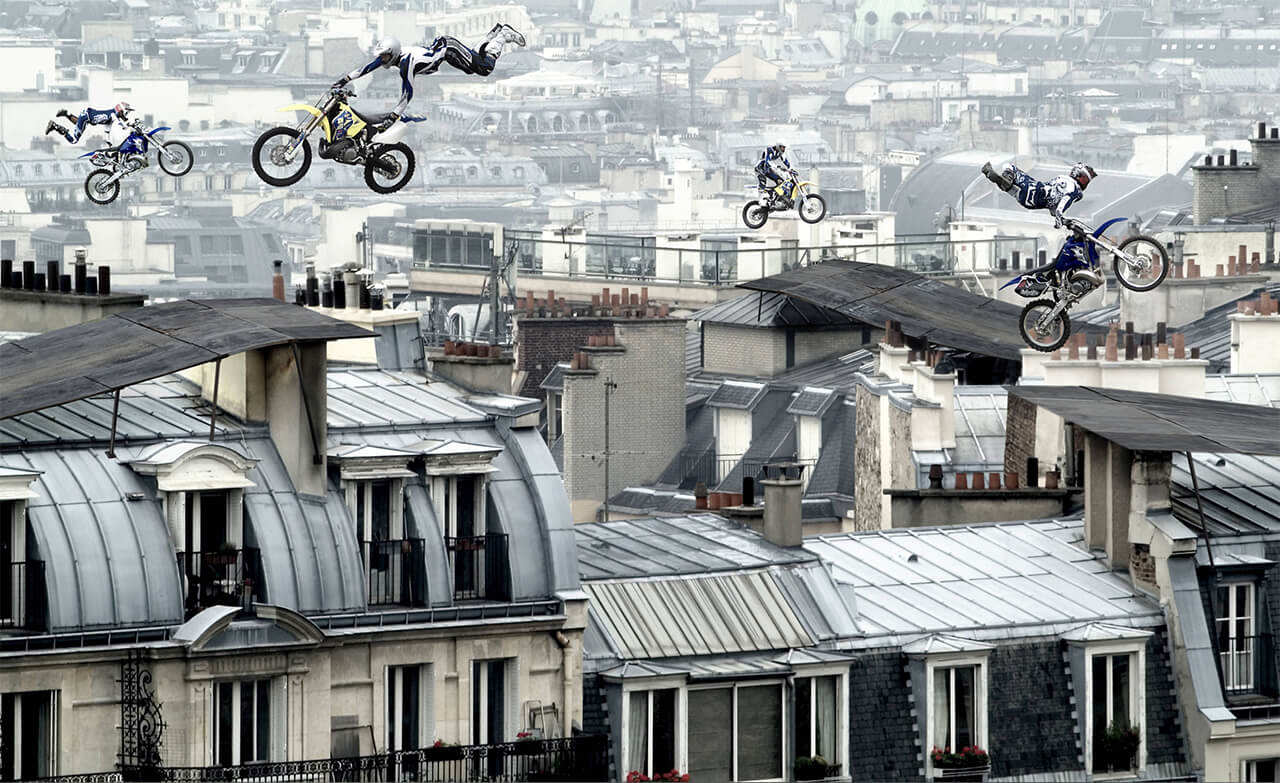 Visualisation of stunt bikes performing acrobats in the sky above a city