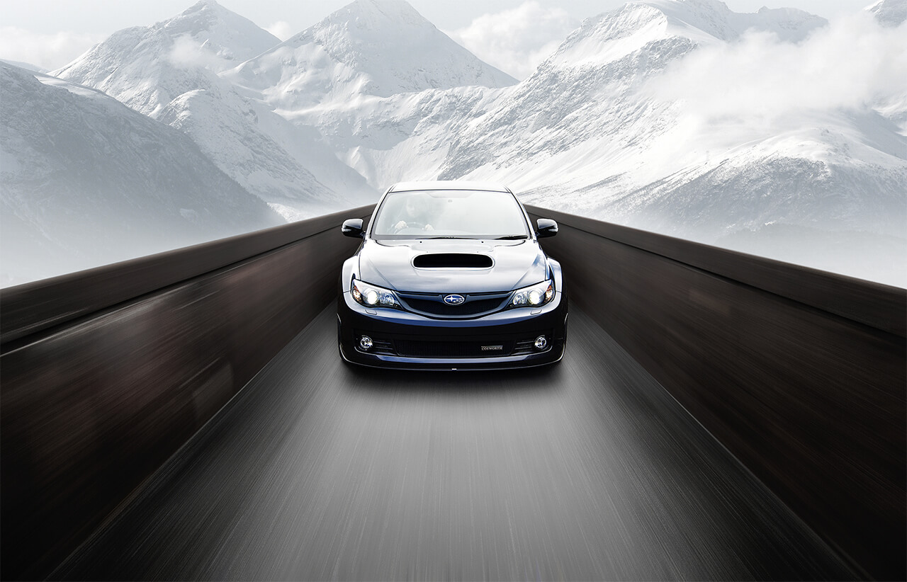 Image of Subaru Sports Car Travelling along a channel with snowy mountains in background