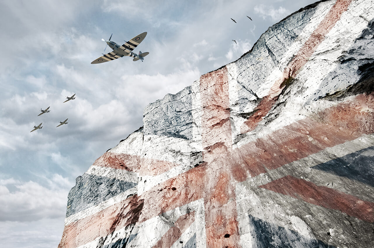 Image of union jack displaying on white cliffs of Dover with spitfire aeroplanes flying over